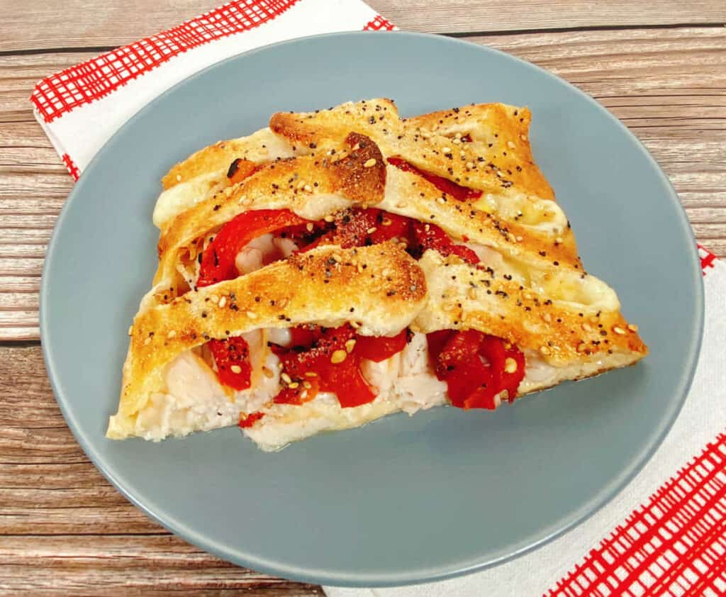 a blue plate sits on a red and white checkered napkin. On the plate is a slice of the braided turkey and red pepper sandwich. Roasted red peppers and turkey peek out from between the braids of pizza dough. The bread is toasted and golden and sprinkled with everything bagel seasoning.