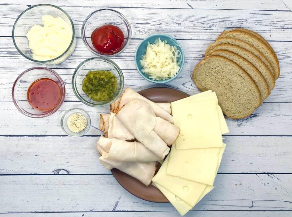 ingredients for turkey reuben sandwich - rye bread, deli turkey, swiss cheese, sauerkraut and thousand island dressing