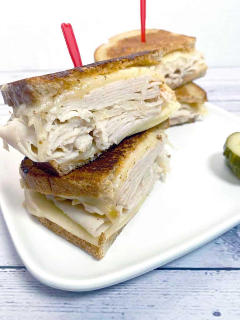 grilled turkey reuben sandwich on white plate