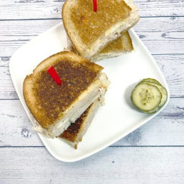 grilled turkey reuben sandwich on white plate with white wood background