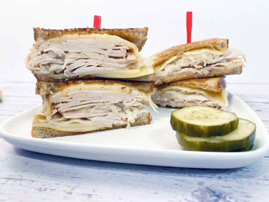 front facing image of turkey reuben sandwich with layers of turkey, swiss cheese and sauerkraut between toasted rye bread