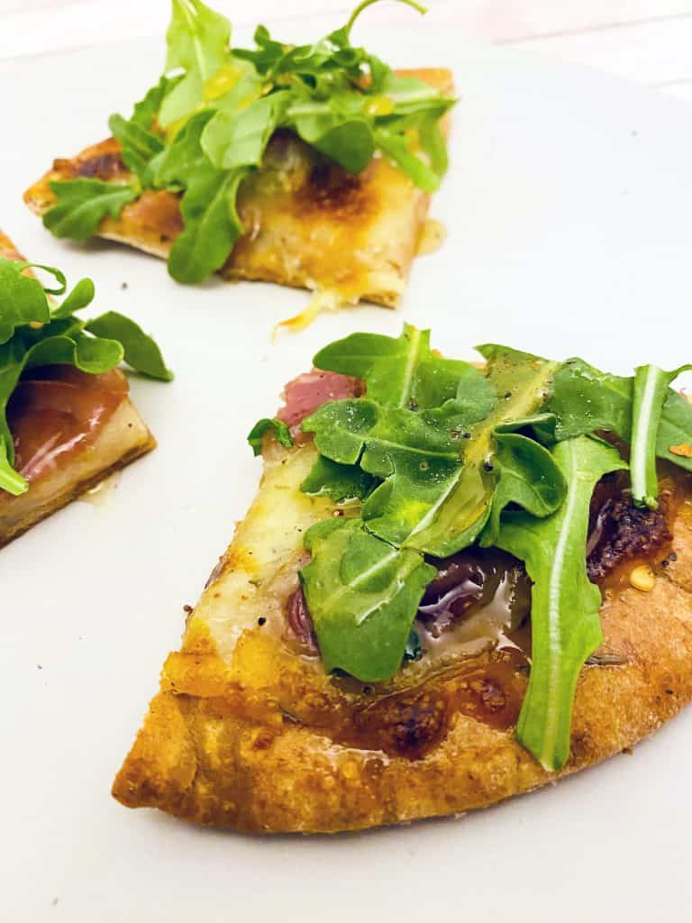 Prosciutto and Arugula are the toppings for this personal sized pizza made on a pita bread