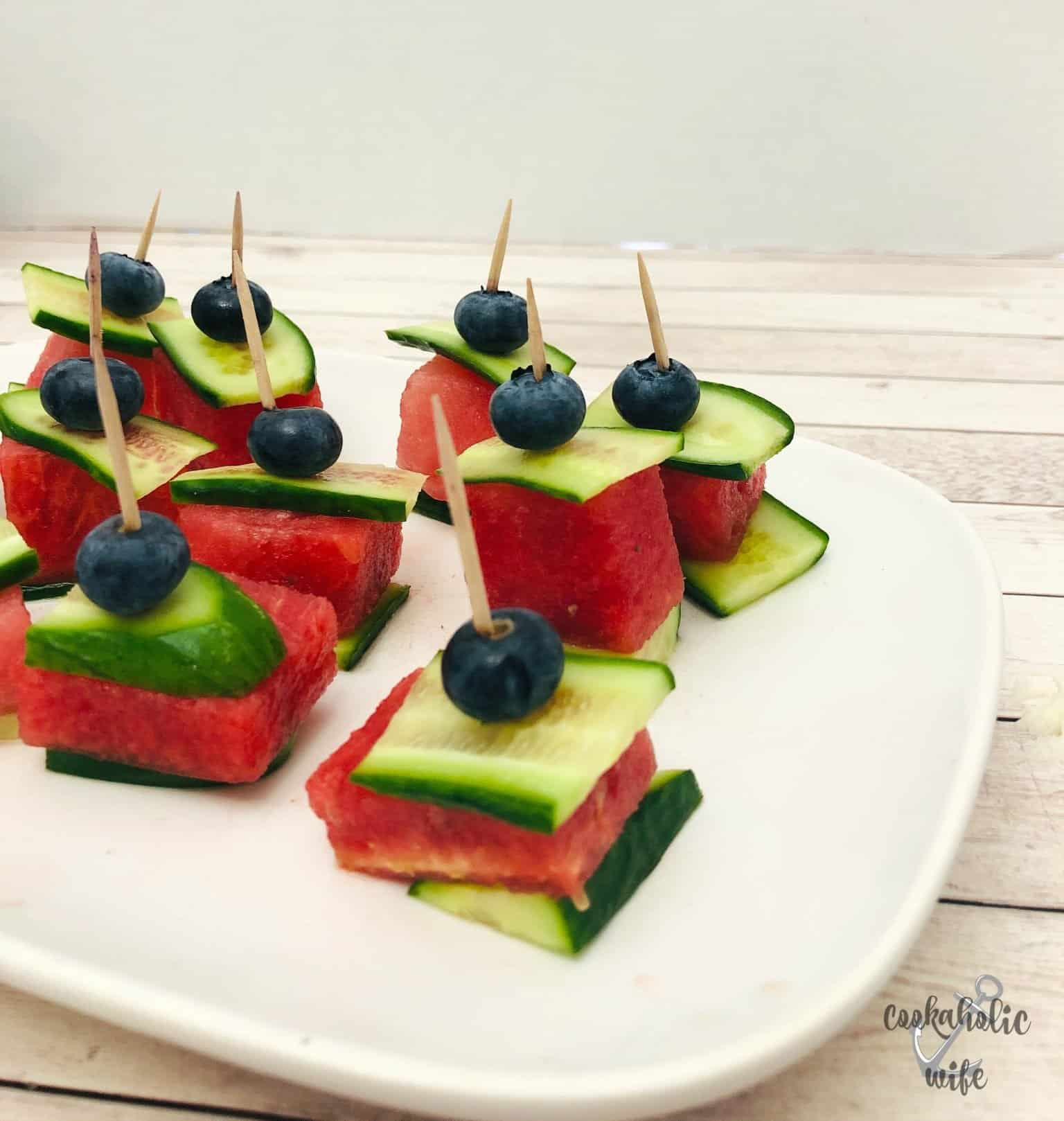 watermelon squares layered between slices of cucumber with a blueberry on top