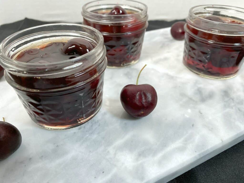 mason jars of cherries soaked in bourbon for cocktails