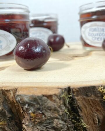 mason jars of cherries soaked in bourbon on a tree stump