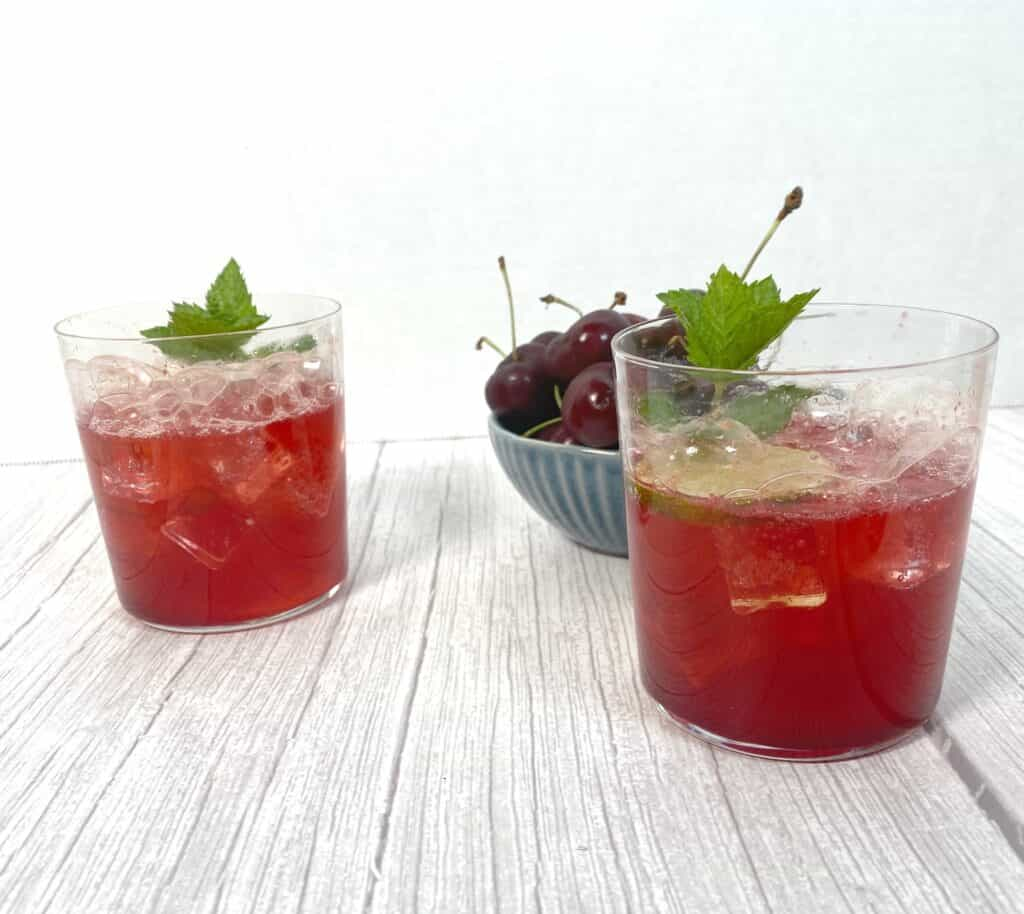 cherry lime bourbon cocktail in glasses on white wood background. bowl of fresh cherries in background