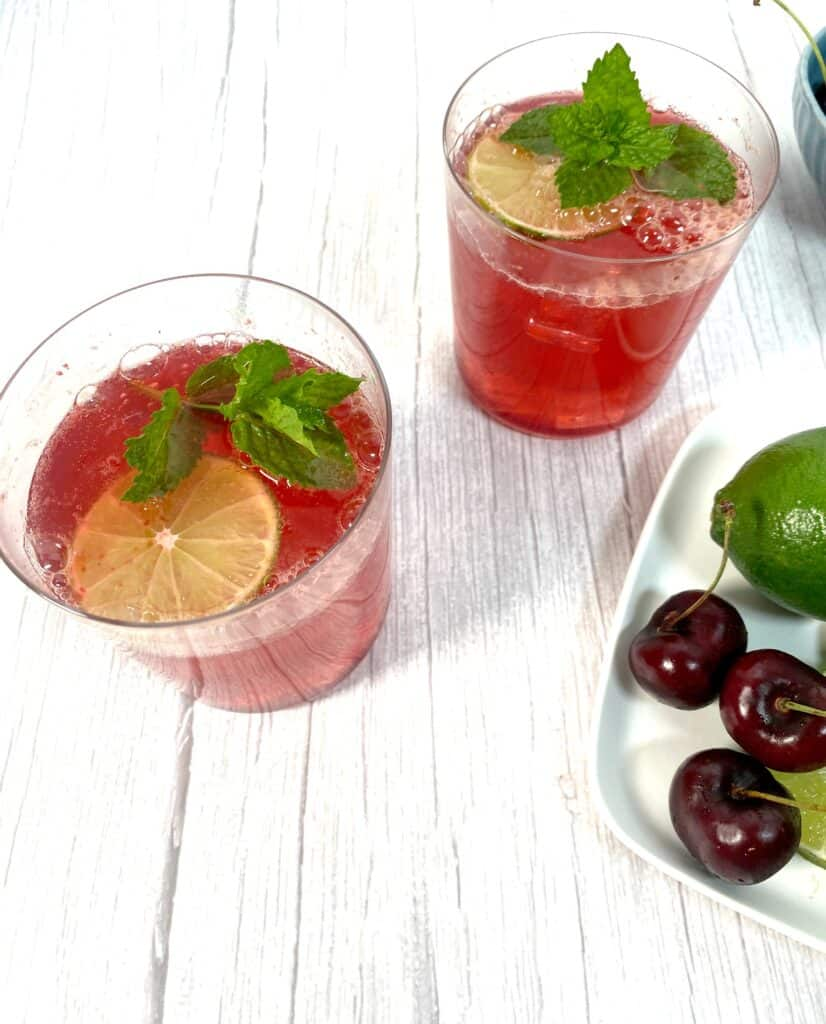 cherry lime bourbon cocktail in glasses on white wood