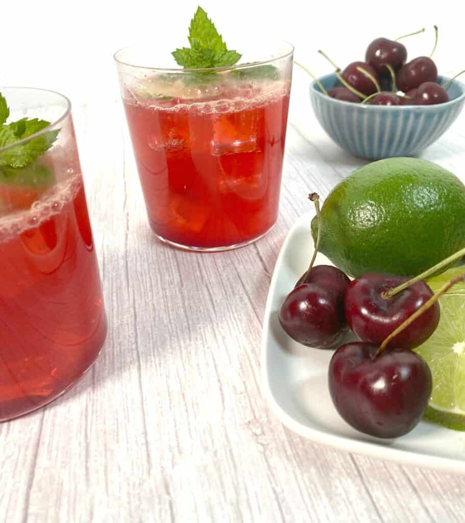 cherry bourbon lime cocktail in glasses with extra cherries and limes