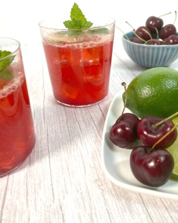 cocktail glasses filled with cherry juice, lime juice, bourbon and soda on a white wood background
