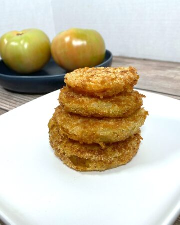 crispy, golden fried green tomatoes stacked four high on a white plate.