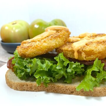 open faced fried green tomatoes sandwich with lettuce and bacon