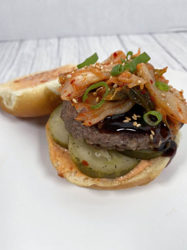 beef burger topped with korean bbq sauce, kimchi and diced green onions. burger is sitting open face to show top bun covered in spicy mayo.
