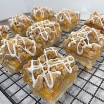 black wire rack with peach crumb bar squares on top. Shortbread crust is visible followed by layer of chopped peaches then topped with a crumble. White glaze zigzags on top of each bar.