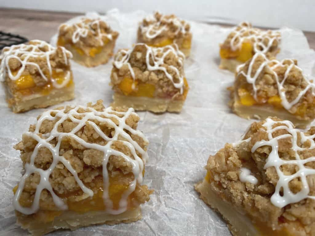 white parchment paper background. Peach crumb bar with visible layers of peaches and oat crumble, topped with zigzag vanilla glaze.