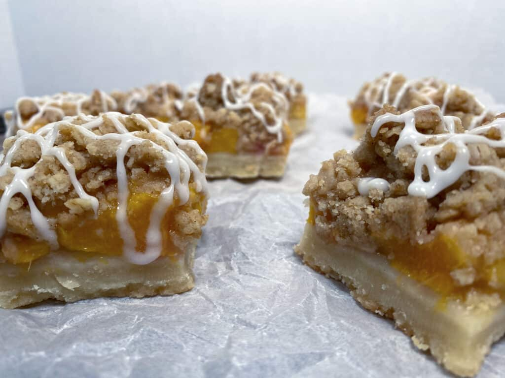 peach crumb bar squares on top. Shortbread crust is visible followed by layer of chopped peaches then topped with a crumble. White glaze zigzags on top of each bar.