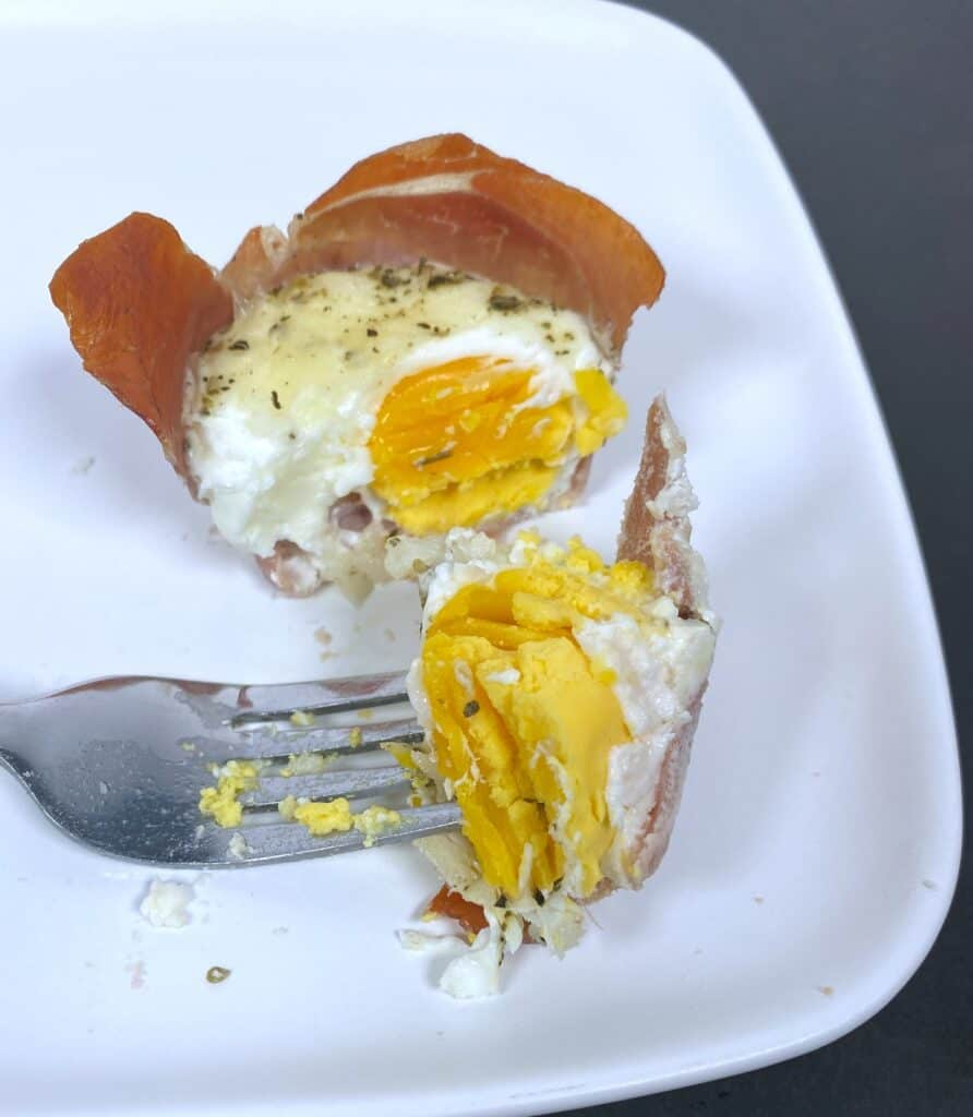 White plate - prosciutto egg cup is cut in half, showing the soft boiled yolk inside.
