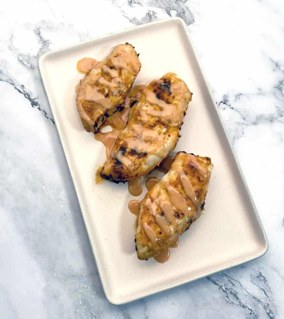 baked chicken breast drizzled with spicy bbq sauce, sitting on a rectangle platter with a marble background
