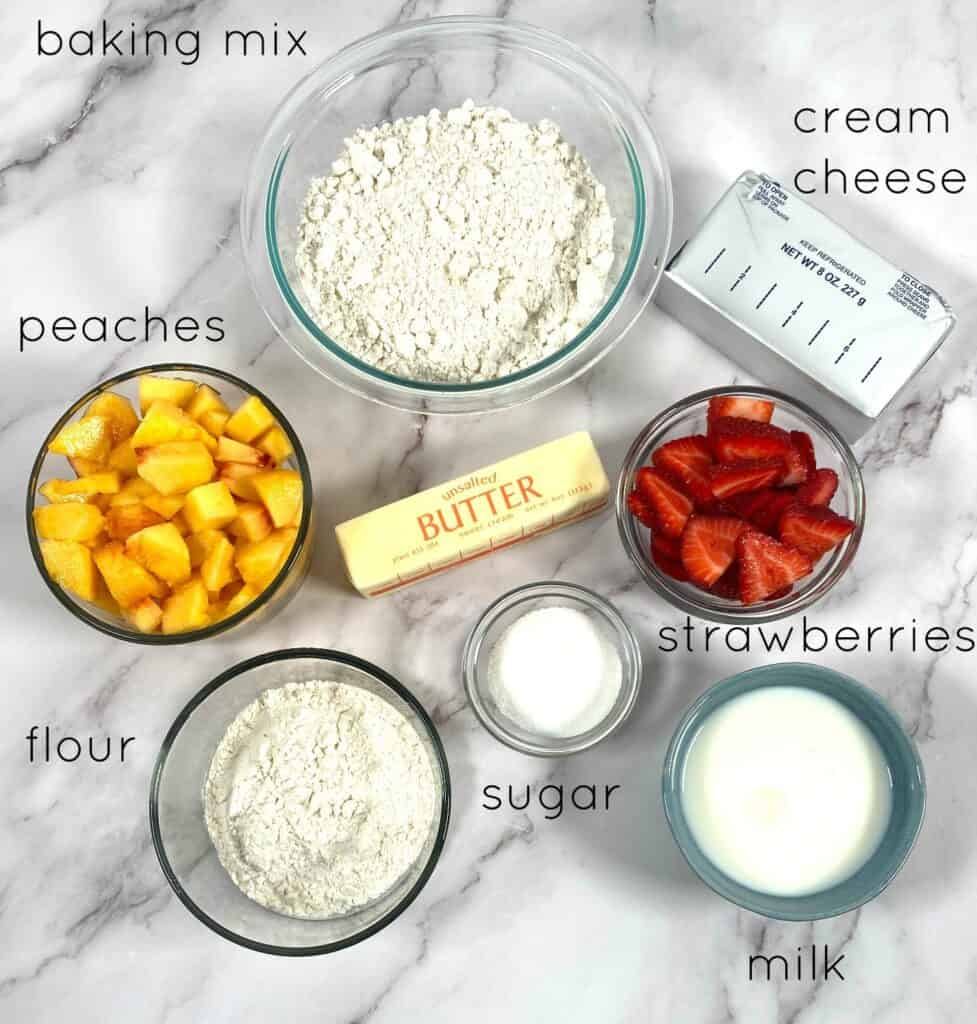 ingredients for peach and strawberry breakfast braid laid out: peaches, strawberries, milk, butter, cream cheese, sugar, flour and baking mix