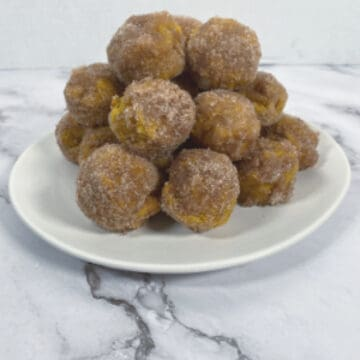 baked pumpkin donut bites covered in cinnamon sugar on white plate, marble background