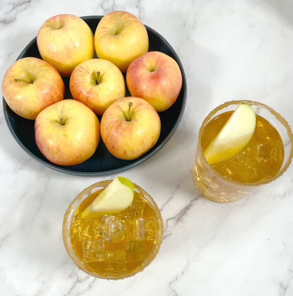 caramel apple whiskey sour cocktails with bowl of apples behind them