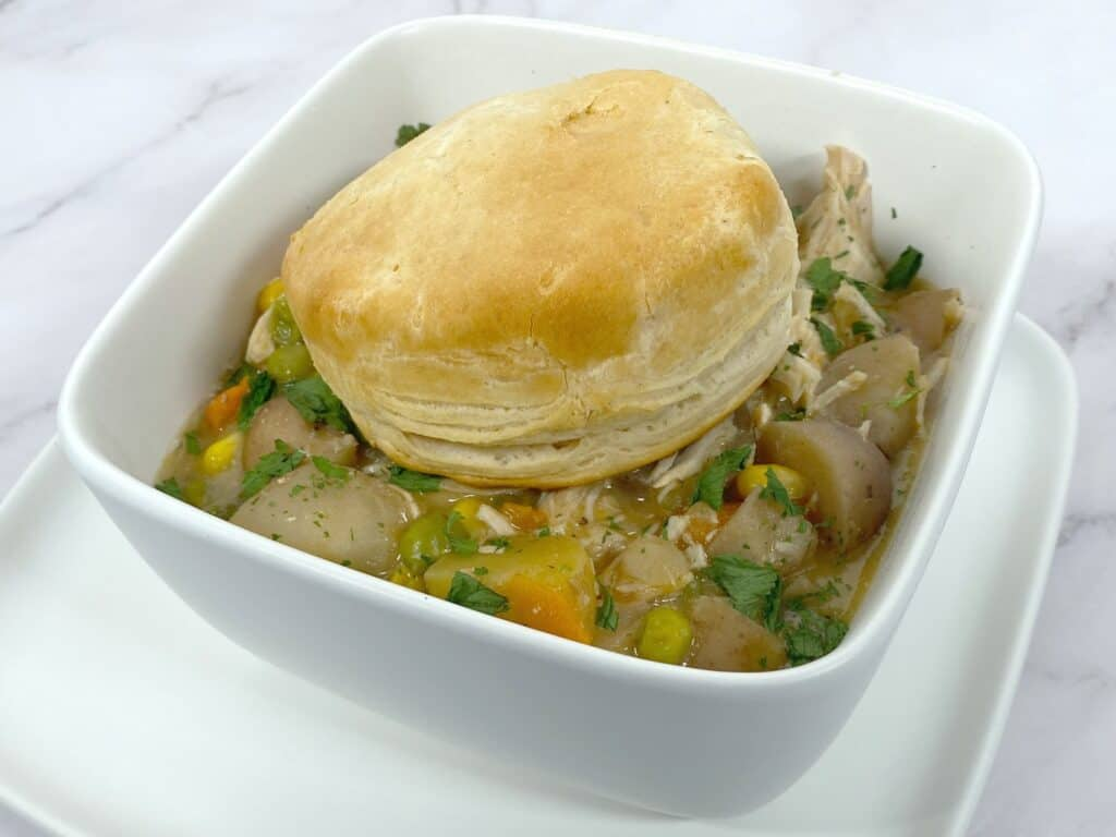 creamy chicken pot pie in a white, square bowl with a browned biscuit on top
