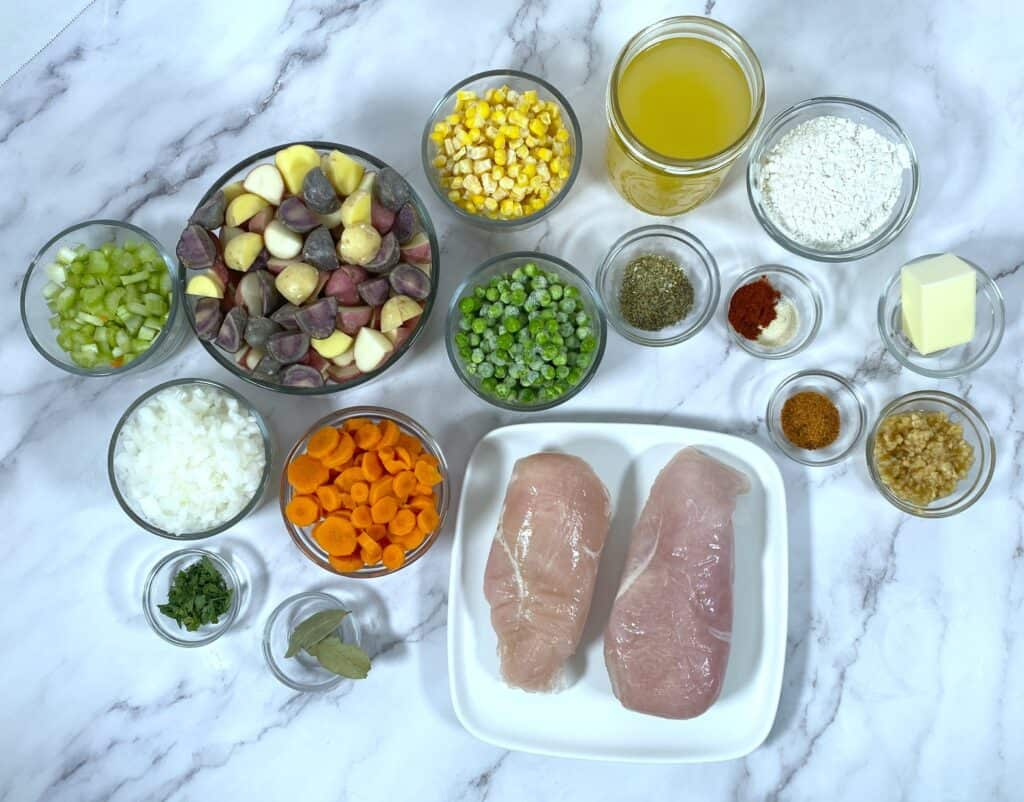 ingredients for chicken pot pie, including chicken breasts, carrots, potatoes, celery, peas, carrots and seasonings