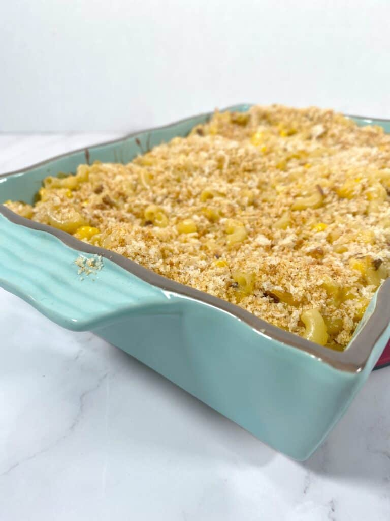 side angle picture of corn macaroni and cheese casserole in a teal dish