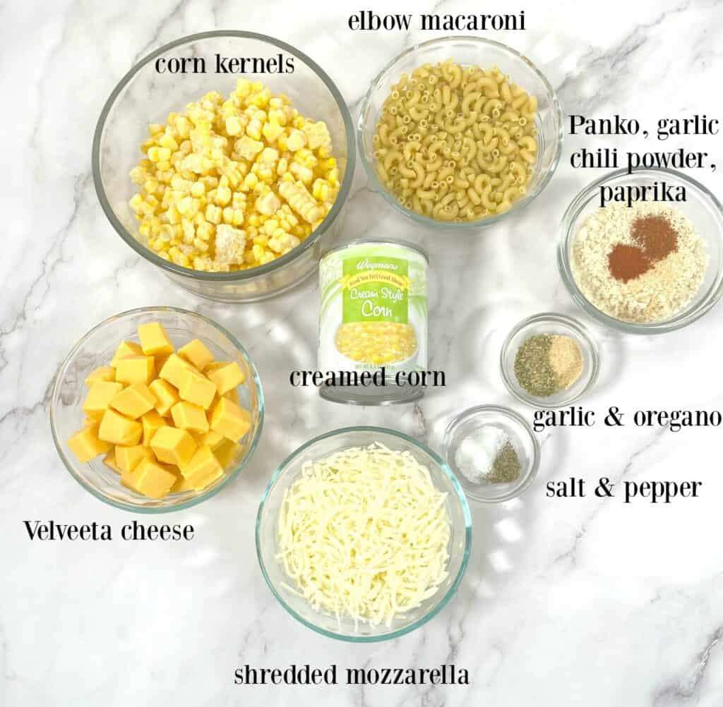 ingredients laid out on marble background to make corn macaroni and cheese casserole
