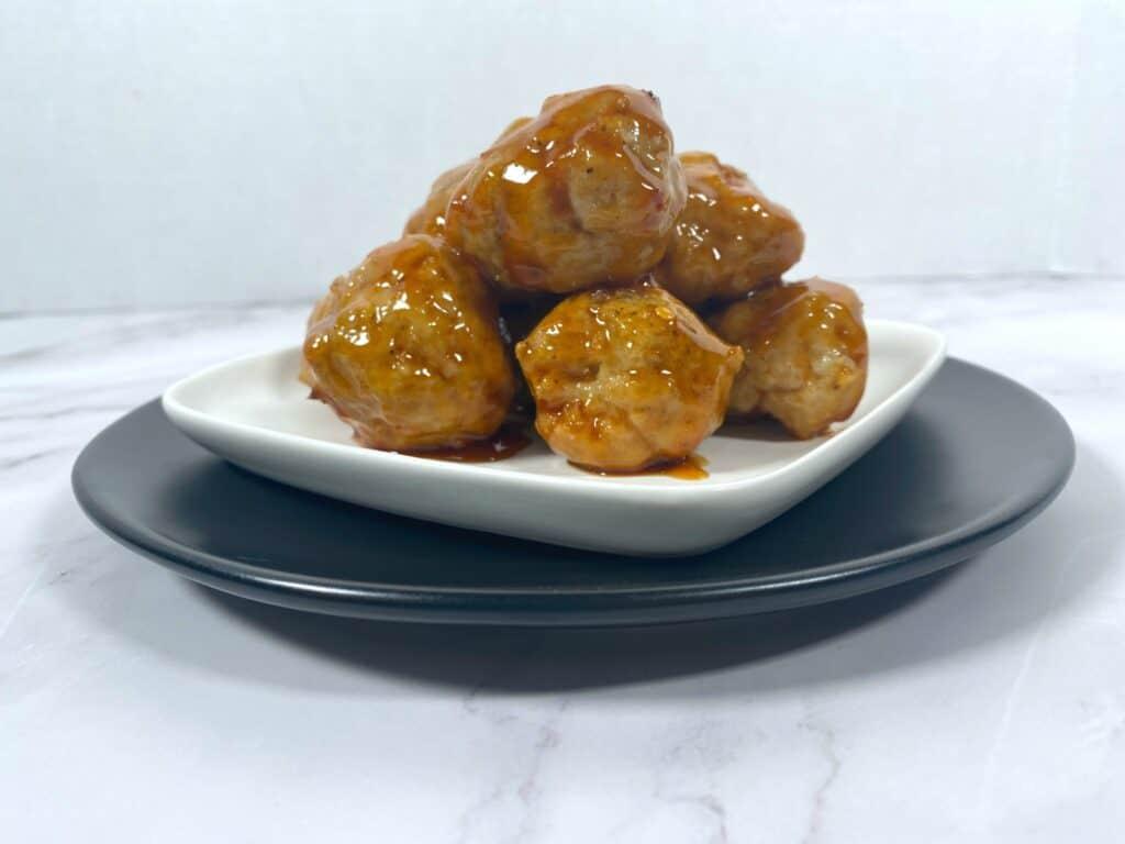 firecracker chicken meatballs piled up on a white plate