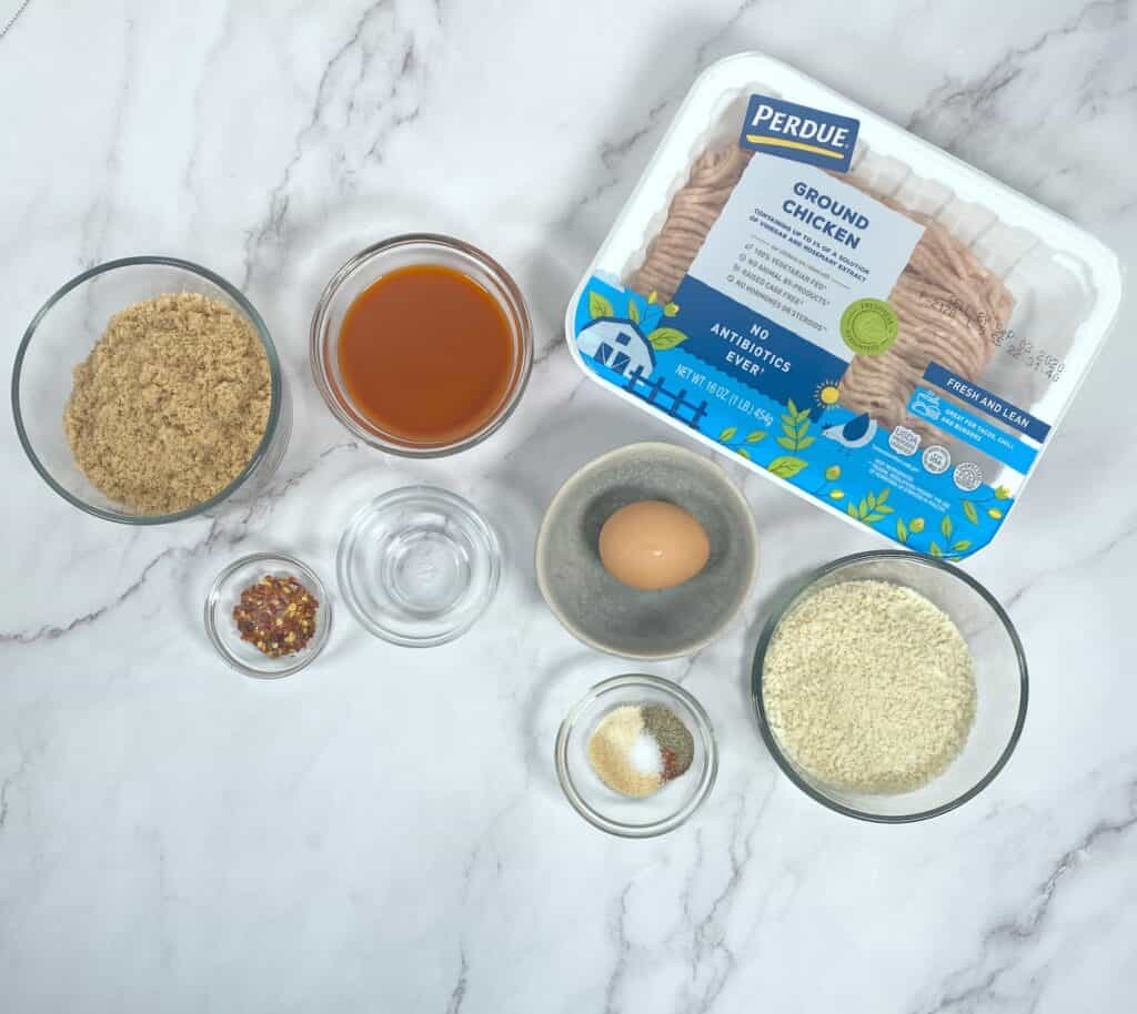 firecracker chicken meatball ingredients on marble background - including ground chicken, panko bread crumbs, egg, spices, wing sauce, brown sugar, crushed red pepper and more.