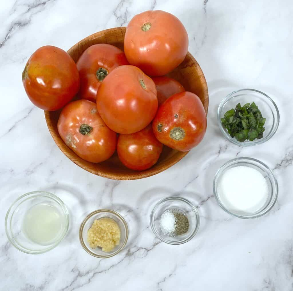 ingredients for homemade canned tomato sauce - tomatoes, garlic, parsley, basil, lemon juice, etc.