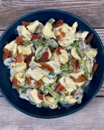 mushroom and asparagus tortellini with parmesan cheese in a blue bowl