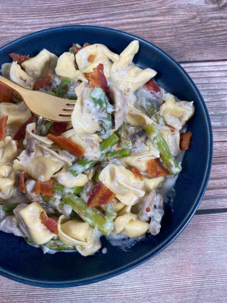 asparagus and mushroom tortellini in a blue bowl