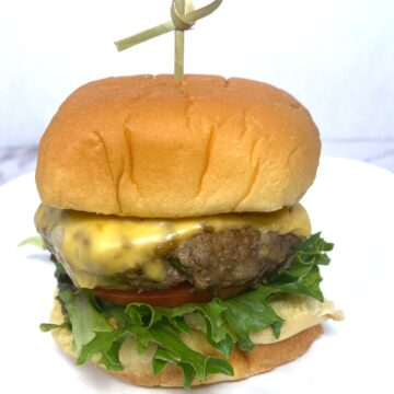 old bay seasoned burger topped with lettuce, tomato and cheese
