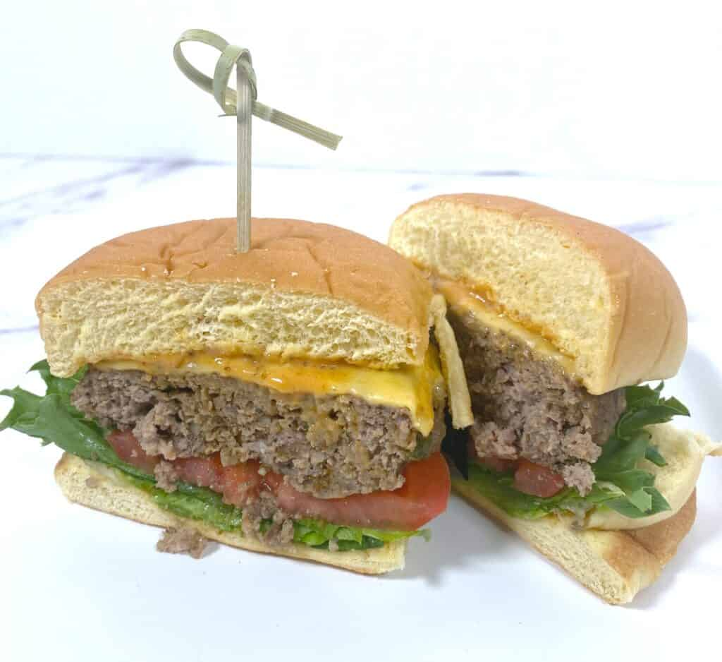 old bay burger with lettuce, tomato and cheese, sliced in half