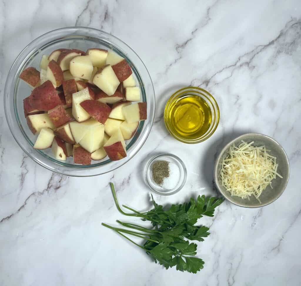 ingredients for parmesan parsley roasted potatoes - baby potatoes, olive oil, parmesan cheese, parsley, salt and pepper; on a marble background