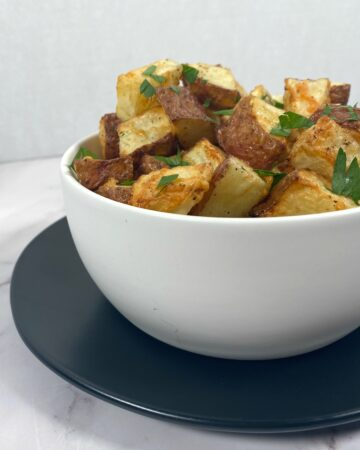 parmesan parsley roasted potatoes in white bowl