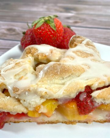 peaches and strawberries nestled in braided dough with a white glaze on top