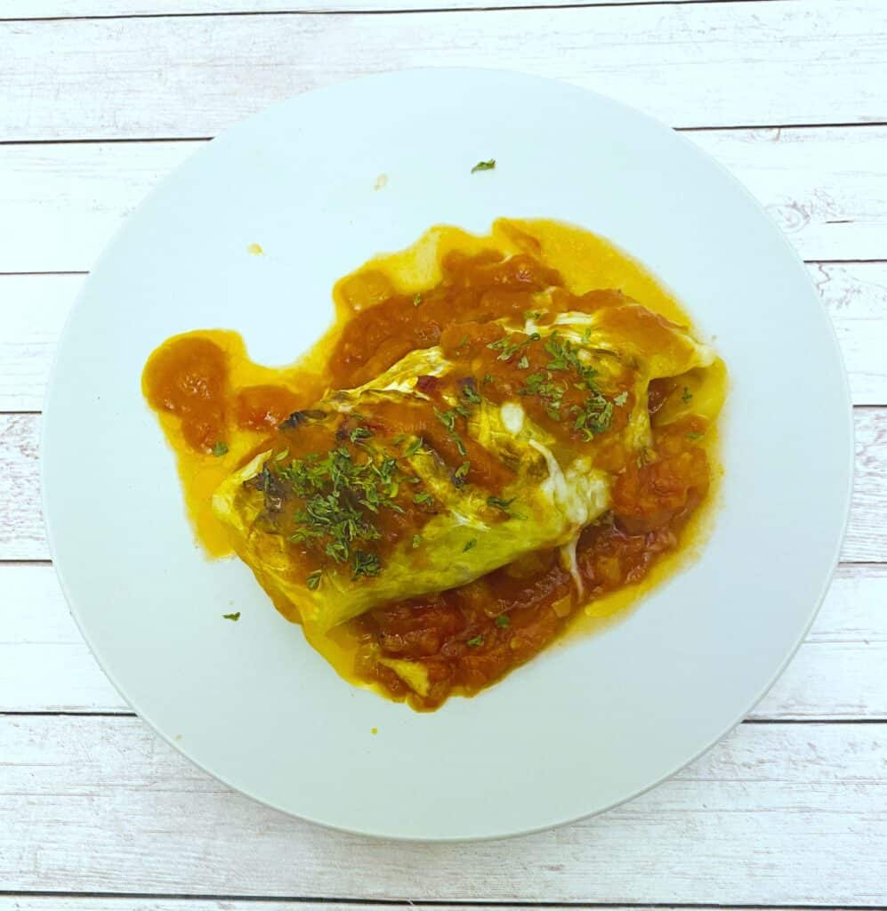 stuffed cabbage roll on top of tomato sauce on white plate