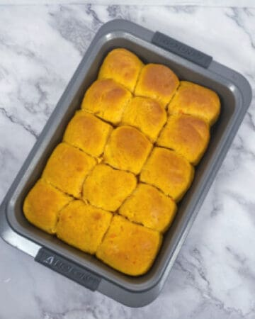 sweet potato dinner rolls, baked, in a 9x13 baking dish on a marble background