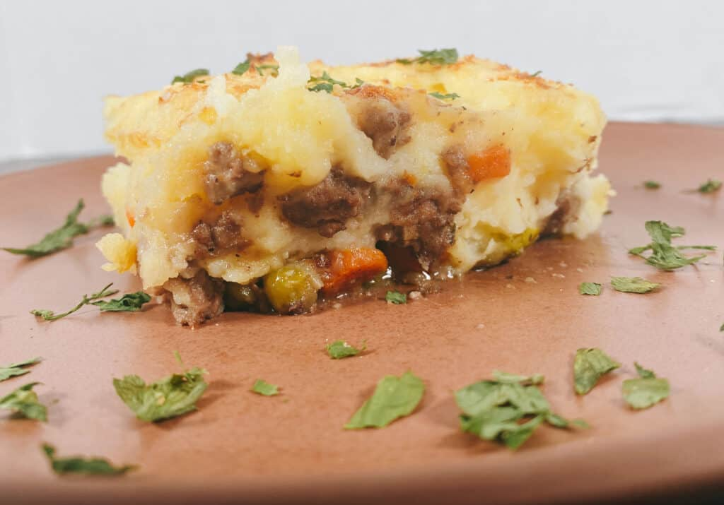 Slice of shepherd's pie on a copper colored plate. Cheesy mashed potatoes are layered on top of a meat and veggie filling. The plate is garnished with parsley.
