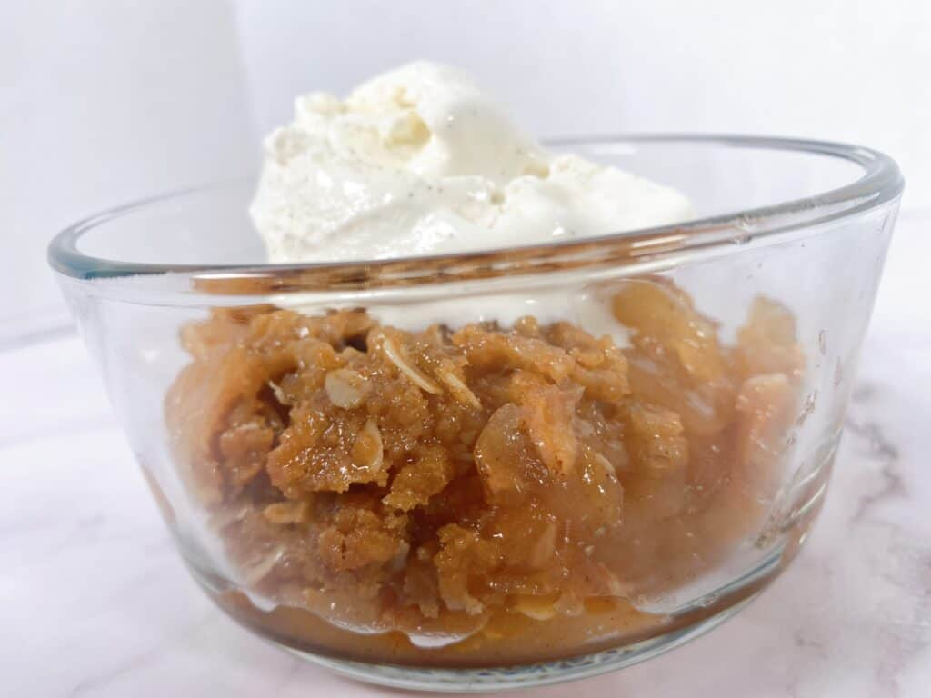 old fashioned apple crisp in a glass bowl with a scoop of vanilla ice cream on top