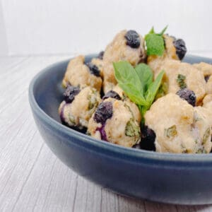 bowl of blueberry chicken meatballs with fresh basil leaves