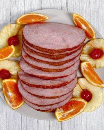 Ham, coated in a brown sugar and mountain dew glaze, sits sliced on a platter, surrounded by pineapple rings, maraschino cherries and orange wedges.