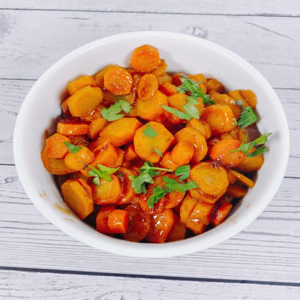 cardamom brown sugar carrots topped with fresh parsley in a white bowl