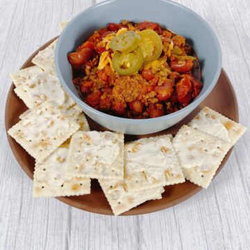 a blue bowl filled with beef chili, topped with shredded cheese and pickled jalapenos sits on a terra cotta colored plate surrounded with buttered saltine crackers