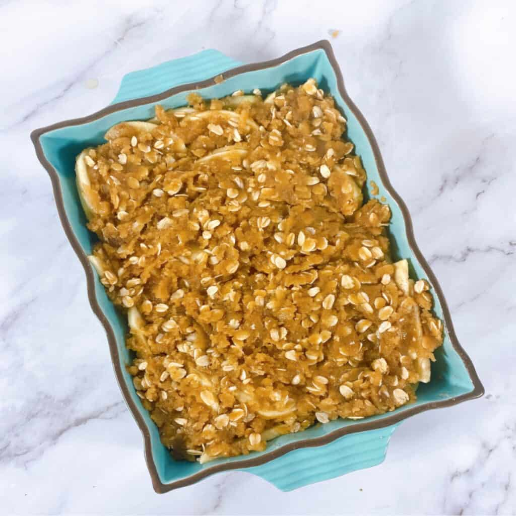 old fashioned apple crisp in a teal baking dish on a marble background
