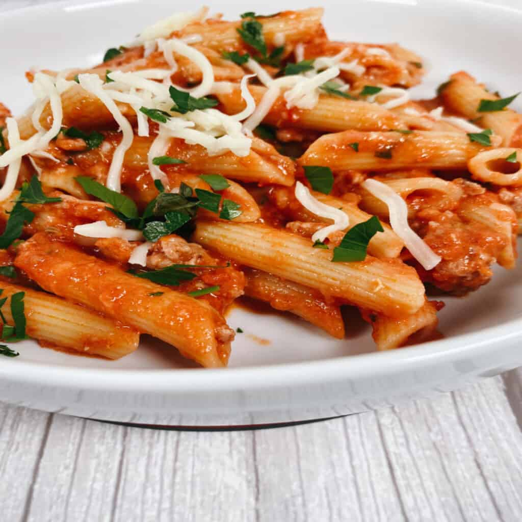 Bowl of penne with vodka sauce, topped with fresh parsley and cheese