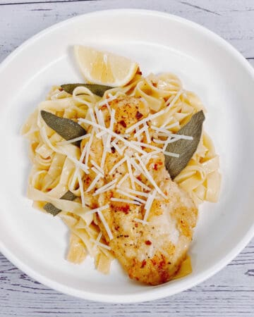 chicken cutlet on a bed of fettuccine pasta with fried sage leaves and a squeeze of lemon