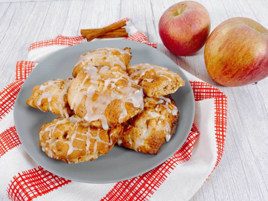 Air fryer apple fritters sit on a blue plate with a red and white checkered napkin. Apples and cinnamon sticks surround them.